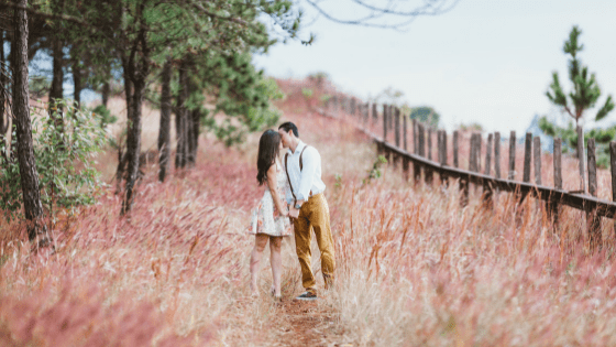 a couple kissing in a field of flowers